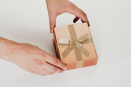 Hands understand the cover of a beautiful box for a gift with a bow from a gold ribbon on a white background close-up