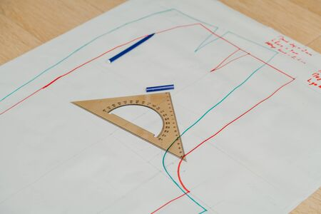 Still life on the sewing pattern. On the paper sheet drawn silhouette of a garment. On top is a triangular ruler. 스톡 콘텐츠