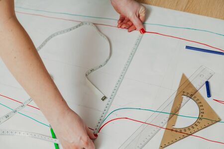 Designer creates a model. Female hands with a manicure do the layout of the sewing piece on paper with a flexible centimeter.