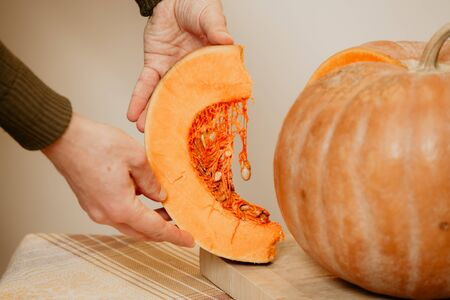 Hands of a man holding a slice of ripe pumpkin. A large round pumpkin stands nearby on a square cutting board. A seed weighs on the inner fibers