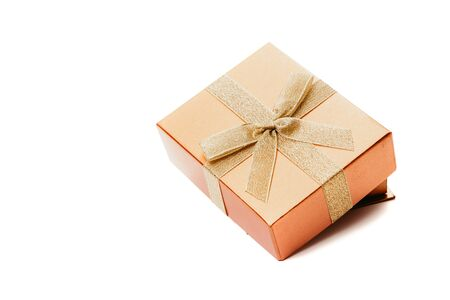 Beautiful box for a gift with a bow from a gold ribbon on a white background close-up. The lid lies on the box at an angle Reklamní fotografie