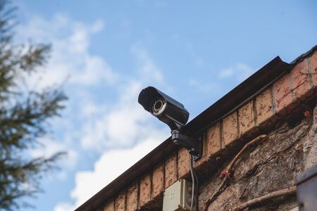 surveillance video camera is mounted on a brick fence against a blue sky with white clouds. Bottom view