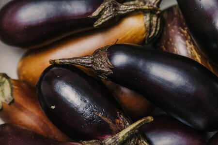 group of blue and brown ripe eggplants with green ponytails lie on top of each other.