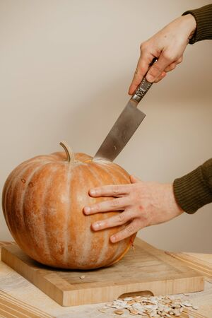 Hands of a man cut a large round pumpkin with a large knife on a square cutting board close-up. Nearby lies a handful of white seeds Reklamní fotografie