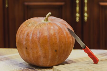 yellow ripe round pumpkin lies on a table with a tablecloth. A knife with a red handle rests on it