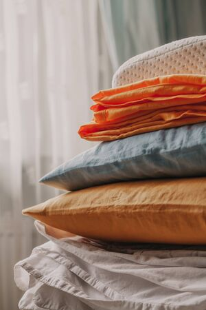 Linens and pillows of different colors and sizes are stacked in front of the bedroom window Reklamní fotografie