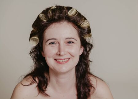 Female portrait without retouching with its natural imperfections. Long hair twisted on curlers Reklamní fotografie