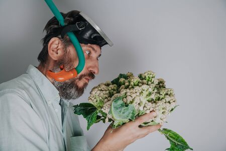Cauliflower or coral. Comic story. A man with a beard and a swimming mask holds a cauliflower head in his hand like sea coral Reklamní fotografie