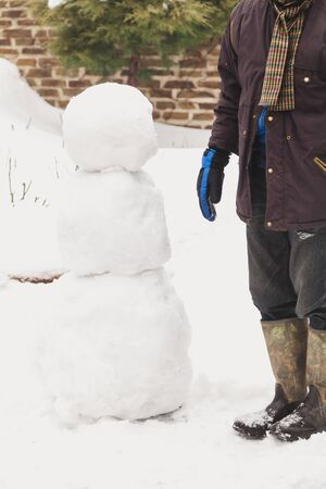 make a snowman. a man in ski gloves sets a third of snow on two lower big comas