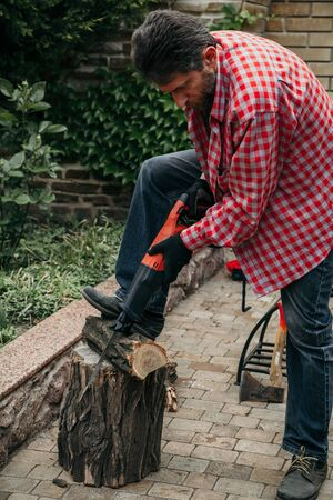 man in a red plaid shirt is sawing a log with a saber electric saw. The right leg presses the log to the stump Reklamní fotografie