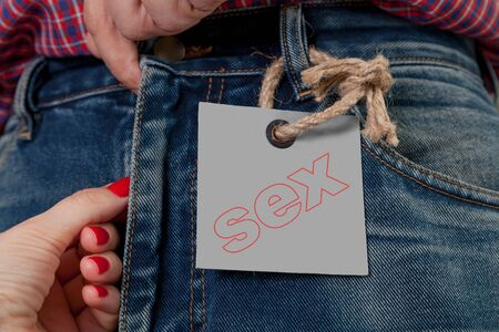 Before sex. A female hand with red manicure unzips the man's jeans with a zipper. On the left is a gray paper label. The word sex is written on the tag