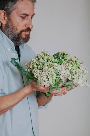 man with a beard is holding a cauliflower head in close up