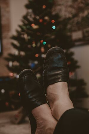Two bare feet in black leather slippers lie on sheeps clothing. Decorated Christmas tree in the background Reklamní fotografie