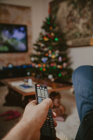 New Year at home. A hand holds a remote control closeup. In the background is a Christmas tree with toys