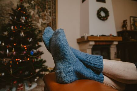 Rest of Santa Claus. Two legs in blue woolen socks lie on a leather sofa against the background of a Christmas tree and a fireplace