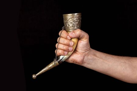 right hand of a man holds a souvenir horn for alcoholic drinks on a black background. The edges of the horns inlaid with metal