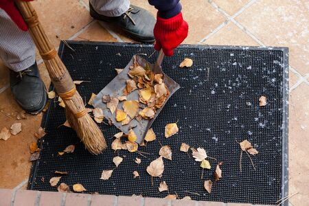 Hands collect birch leaves with a broom on a metal spatula from a rubber mat in front of the steps. The first snow lies on the tile