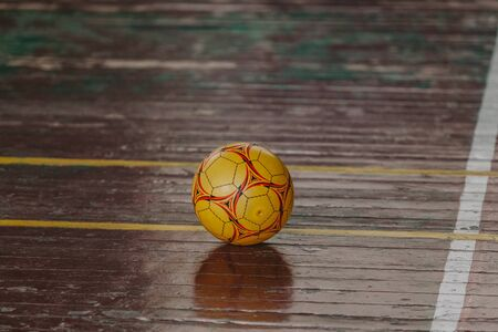 Binnen sporten. De gele bal ligt op de bruine houten vloer van de hal om te oefenen. Lijnmarkeringen worden op de vloer getekend