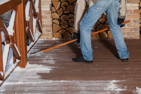 Cleaning on the winter terrace. The owner brushes the floor of the veranda from snow on a wooden handle. Firewood stacked in the background Stock Photo