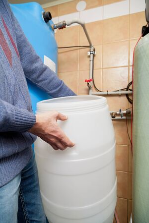 Plumber hands hold round plastic osmosis water treatment system water tank
