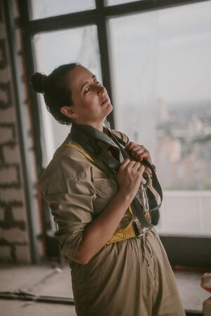 Nice girl in gray overalls holds in her hands a safety belt with a carbine on the background of the window. Portrait of a woman without retouching with her natural imperfections