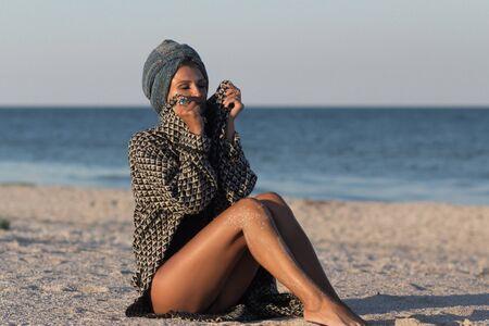 Woman model in turban and summer knitted coat sitting on sandy sea beach Foto de archivo