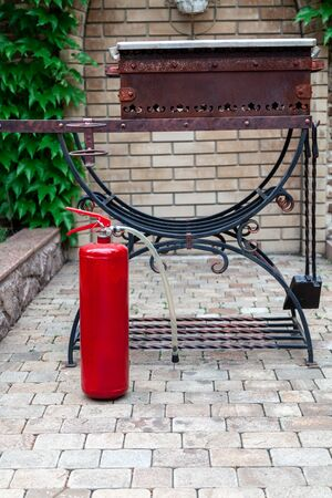 Safety at a picnic. A large red fire extinguisher stands in front of a forged barbecue in the courtyard Stockfoto