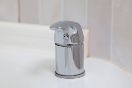 Chrome-plated metal lever mixer mounted on the bathroom close-up
