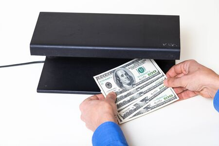 Hands verify the authenticity of dollar bills with a detector on a white background close-up