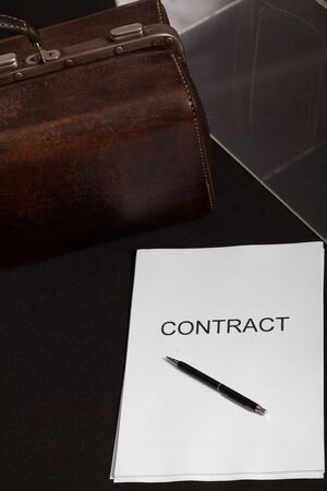 Contract at auction. Close-up of a contract printed on paper and a leather carpetbag. The pen is on top of the contract