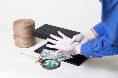 currency check begins. Hands put on rubber gloves before authenticating dollar bills. Nearby is a large magnifier and a metal detector. Worth a roll of rope