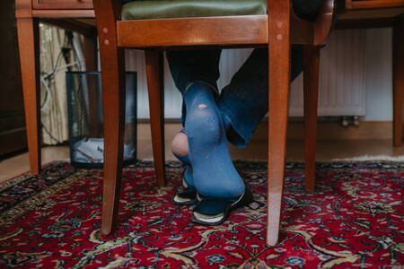 Holes in socks. A man sits on a wooden chair in the office in slippers on his both socks; you can see big holes sock, full of holes, hole, table, chair, office, carpet, furniture, Stock fotó