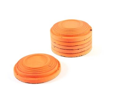 Several round orange targets of cymbals are stacked on a white background. One plate lies in front of the stack. Close-up