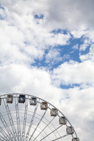 Viewing attraction. Cabins on the Ferris wheel against the blue sky with white clouds Stock fotó