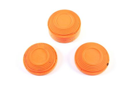 Several round orange targets of cymbals are stacked on a white background. Two plates lie in front of the stack. Close-up