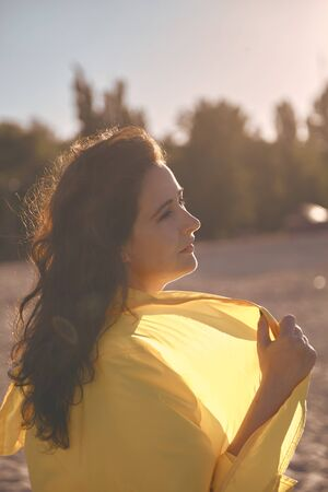 Portrait of a pretty girl with long red hair and a bright yellow jacket on a sandy beach  Stock fotó