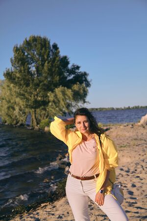 Portrait of a pretty girl with long red hair and a bright yellow jacket on the sandy beach of a wide river