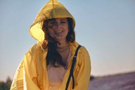 Portrait of a pretty girl with long red hair and a bright yellow jacket against a blue sky  Stock fotó