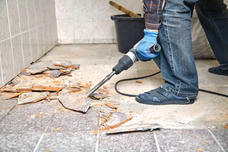 construction puncher with a long flat peak destroys the floor tiles in a small room. Close-up Фото со стока