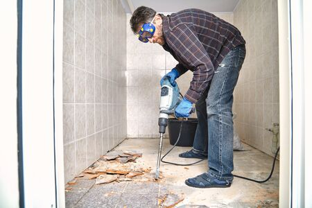 man in a plaid shirt destroys the floor tile with a construction puncher in a small room