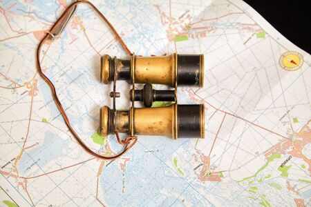 Still life with binoculars and a map. Vintage metal binoculars lie on topographic map of the area. A compass is drawn on the map
