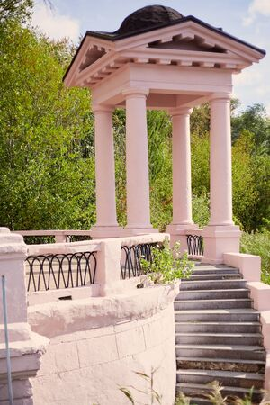 small pink arbor on four columns and an observation deck in the autumn park. A stone staircase descends from it.