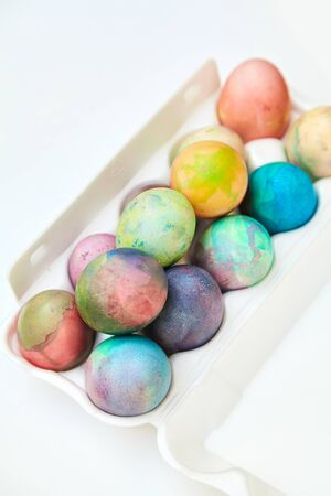 Attribute Easter holiday. Chicken eggs originally painted in different colors are in a plastic container with cells.