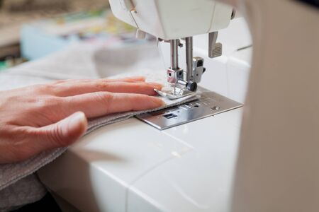Seamstress at work. Seamstress's left hand makes a seam on a soft fabric using a sewing machine close-up Reklamní fotografie