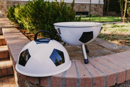 Football picnic. The original brazier in the form of a soccer ball stands on brickwork in the yard Imagens