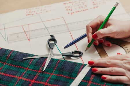 Designer creates a model. Female hands with manicure make markings on a piece of Scottish fabric with a flexible centimeter
