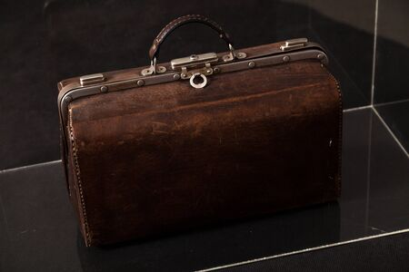 Antique leather carpetbag standing in a glass box