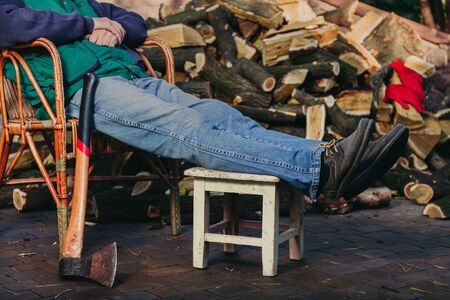 man is resting in a wicker chair in the yard in front of a pile of chopped firewood. Nearby is an ax on a long handle