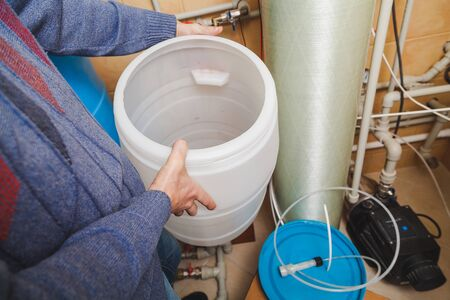 Plumber's hands hold round plastic osmosis water treatment system water tank Stock fotó