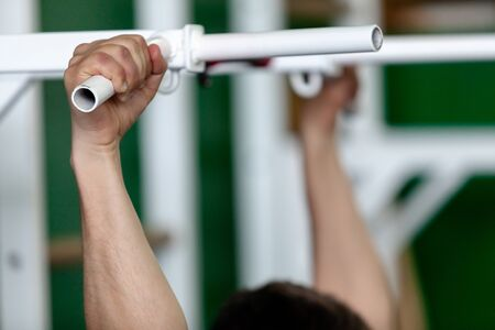 Gymnast's hand hold tightly on a horizontal bar of a metal exercise machine in a sports hall close-up